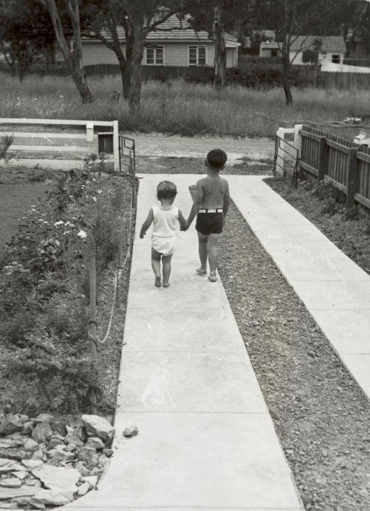 Boy Takes Sister for Walk Down Driveway of Home, Blackburn, 1953. Source Museum Victoria.